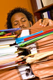 Young African American Male Buried in Work. A young African American male buried in work looks through the stacks of colorful folders piled on top of his desk Stock Photos