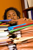 Young African American Male Buried in Work. A young African American male buried in work looks through the stacks of colorful folders piled on top of his desk Stock Photo