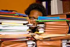 Young African American Male Buried in Work. A young African American male buried in work looks between the two stacks of colorful folders piled on top of his Royalty Free Stock Photography