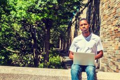 Young African American Male College Student Studying in New York. City, with short hair, wearing white T shirt, sitting by street on campus under sun in summer Stock Photos