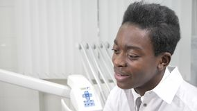 Young African American male doctor dentist. Beautiful girl patient at chair at dental clinic. Medicine, health. Young African American male doctor dentist in a stock video