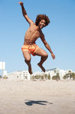 Young african american male jumping at beach. Portrait of a handsome young African American man jumping at the beach Royalty Free Stock Photos
