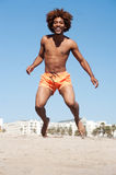 Young african american male jumping at beach Royalty Free Stock Photos