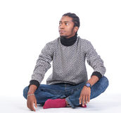 Young African-American male sitting on the ground. Looking to his side in a white background Royalty Free Stock Photo