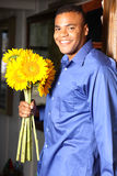 Young African American Male with Sunflowers. At the front door of a house Royalty Free Stock Photo