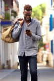 Young african american male traveler walking outside and using mobile phone. Portrait of young african american male traveler walking outside and using mobile Stock Photos