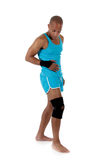 Young African American man athlete, bandaged. Young attractive African American man athlete wearing a wrist brace and knee support, bandaged. White background stock photo
