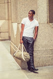 Young African American Man carrying bag, traveling in New York. Street Fashion. Young African American man wearing white V neck T shirt, black pants, leather Royalty Free Stock Images