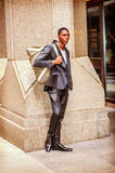 Young African American Man carrying shoulder bag, traveling in N. Street Fashion. Young African American Man wearing black fashionable jacket, black pants Stock Image
