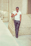 Young African American man carrying shoulder bag, traveling in N. Street Fashion. Young African American Man wearing white V neck T shirt, black pants, leather Stock Images