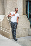 Young African American man carrying shoulder bag, traveling in N. Street Fashion. Young African American Man wearing white V neck T shirt, black pants, leather Stock Photography
