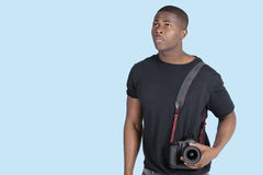 Young African American man with digital camera looking up over blue background Royalty Free Stock Images