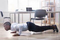 Businessman Doing Pushup In The Office. Young African American Man Doing Pushup In Front Of Closed Glass Door royalty free stock photos
