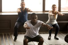 Young african-american man doing squat exercises at group fitnes. Young african american men doing squat exercise at group fitness training, sporty black guy Royalty Free Stock Photos