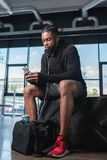 Young african american man in earphones sitting in tyre and using smartphone. In gym stock images