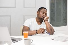 Young African American man falls asleep at breakfast in the kitchen. stock photography