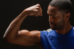 Young African American Man Flexing Biceps. A young African American man flexing his biceps, studio shot Royalty Free Stock Image