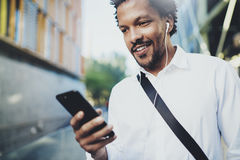Young African American man in headphone walking at sunny city and enjoying to listen to music on his smart phone.Blurred Royalty Free Stock Photography