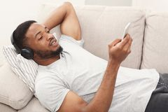 Young african-american man in headphones with mobile stock image