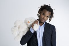 Young African American man holding teddy bear royalty free stock photo