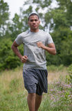 Young African American Man Jogging in the Woods Royalty Free Stock Photography