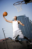 Young  African American man jumping with a basketball on an urban basketball court Stock Photography