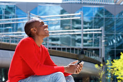 Young african American man laughing outside with mobile phone. Side portrait of young african American man laughing outside with mobile phone Royalty Free Stock Photo