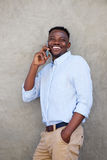 Young african american man leaning against wall talking on cellphone Royalty Free Stock Photos