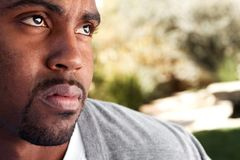 Young African American man looking sad. Young African American man looking sad sitting outside Royalty Free Stock Photo