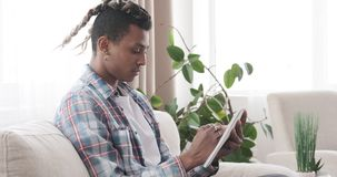 Young man writing in notepad at home. Young african american man preparing shopping list in notepad at home stock video
