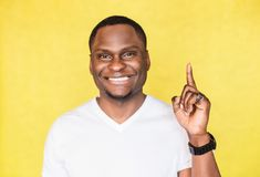 Young African American man raises index finger as gets good idea. royalty free stock photo