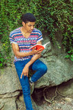 Young African American Man reading book, traveling, relaxing at Royalty Free Stock Images