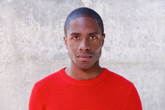 Young african american man in red sweater staring Royalty Free Stock Photography