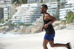 Young african american man running at the beach Stock Photos