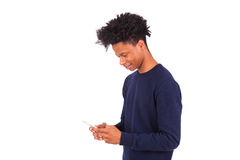 Young African American man sending a sms text message on his sma Stock Images