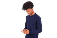 Young African American man sending a sms text message on his sma Royalty Free Stock Photos