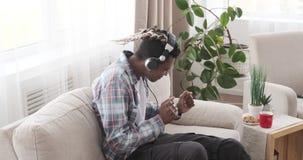 Man singing and listening music on headphones. Young african american man singing and listening music on headphones at home stock video footage