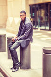 Young African American Man siting on street in New York, relaxin. Young black teenage boy is sitting on street, hunchbacked, sad, tired, looking at you. Man Royalty Free Stock Photo