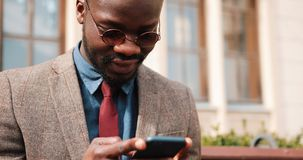 Young African American man sitting on a bench and typing on his smart phone. Business and lifestyle concepts.  stock footage
