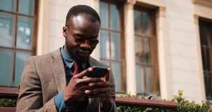 Young African American man sitting on a bench and typing on his smart phone. Business and lifestyle concepts.  stock video footage