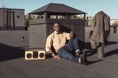 Young african american man sitting on rooftop with boombox and looking. At camera stock photo