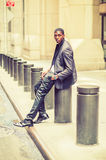 Young African American Man sitting on street in New York, relaxi. City Boy. Wearing fashionable jacket, pants, leather shoes, wristwatch, a hand in pocket, young Royalty Free Stock Image