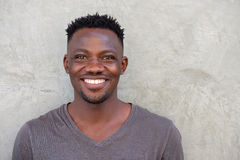 Young african american man smiling by wall Stock Photos