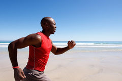 Young african american man sprinting on the beach Stock Photography
