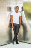 Young African American Man Street Fashion in New York. Street Fashion. Young African American Man wearing white V neck T shirt, black pants, leather shoes, hand Royalty Free Stock Image