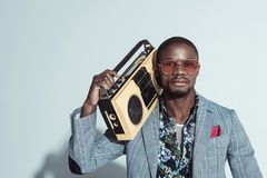 Young african american man in suit and sunglasses, holding a boombox and looking. At camera royalty free stock images