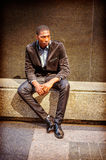 Young African American Man thinking outside in New York. Young African American Man street fashion in New York, wearing black blazer, pants, leather shoes Royalty Free Stock Photos