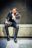 Young African American Man thinking outside in New York. Young African American Man street fashion in New York, wearing black blazer, pants, leather shoes Stock Image