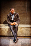 Young African American Man thinking outside in New York. Young African American Man street fashion in New York, wearing black blazer, pants, leather shoes Stock Photo