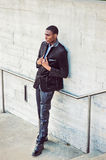 Young African American Man thinking outside in New York. Young African American Man wearing black fashionable jacket, pants, leather shoes, standing against wall Royalty Free Stock Photo